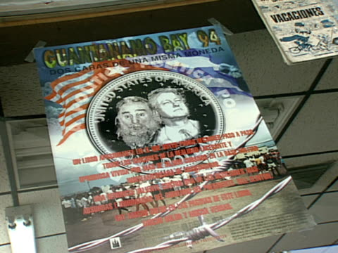poster of guantanamo bay 94 w/ images of bill clinton and fidel castro taped to a window in little havana zo/zi - bay window stock videos & royalty-free footage