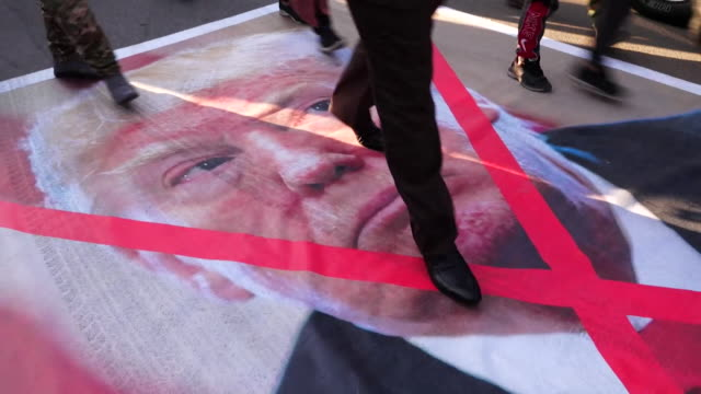 poster of president donald trump, being walked and driven over in baghdad, at memorial to iranian general qasem soleimani and iraqi militia leader... - war and conflict stock videos & royalty-free footage
