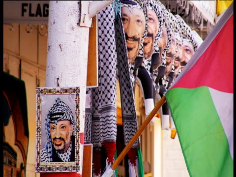 poster of yasser arafat next to stall selling palestinian flags and yasser arafat balloons palestine 2002 - poster stock videos & royalty-free footage