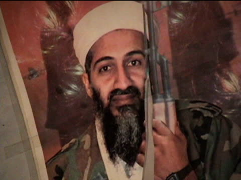 cu poster with usama bin laden holding kalashnikov sakha kot in tribal zone at afghan border federally administered tribal areas pakistan audio - 2004年点の映像素材/bロール