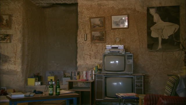 vidéos et rushes de posters, paintings, furniture, and televisions occupy a room in a - messy room