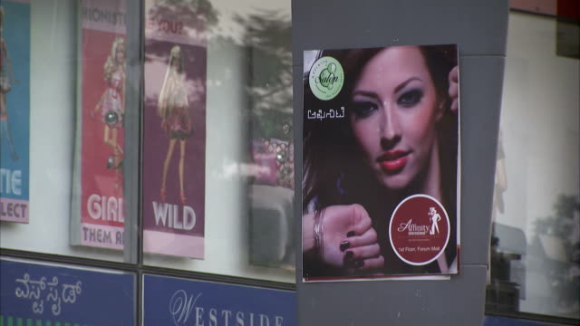 Posters show through a storefront window.
