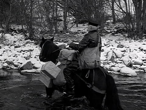 A postman crosses an icy river on a horse in the Scottish highlands