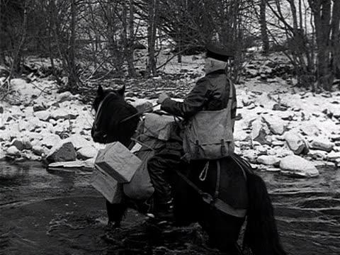 vídeos de stock e filmes b-roll de a postman crosses an icy river on a horse in the scottish highlands - carteiro