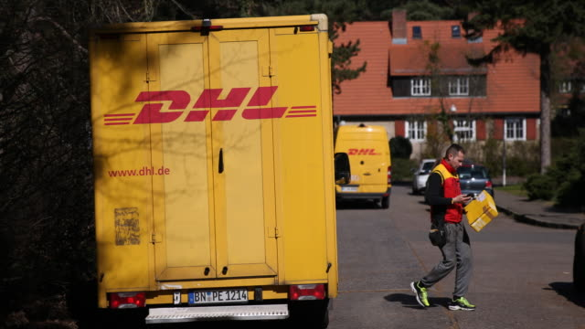 vidéos et rushes de postman delivers parcels in berlin zehlendorf on april 01 in berlin, germany. everyday life in germany has become fundamentally altered as... - achat à domicile