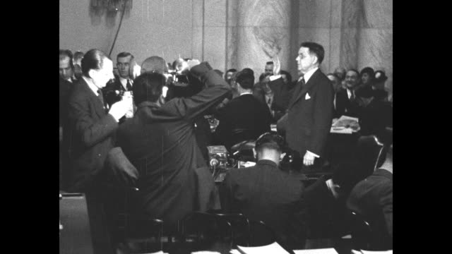 postmaster general walter folger brown is sworn in before testimony to the us senate re: the air mail scandal, as news photographers get pictures /... - 航空便点の映像素材/bロール