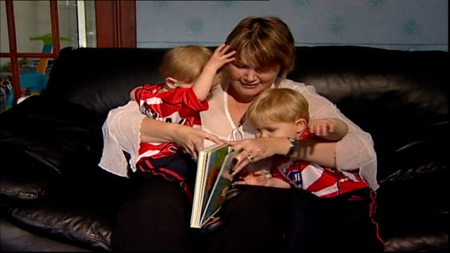 post-natal depression: close up; england: int set-up lindsay yates sitting with young twins reading book - postpartum depression stock videos & royalty-free footage