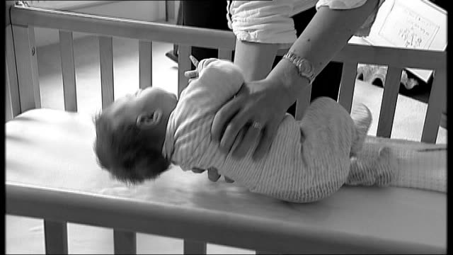 post-natal depression: gene test breakthrough; graphicised sequence baby in cot as picked up by mother - postpartum depression stock videos & royalty-free footage