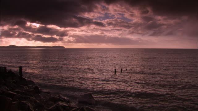 "vidéos et rushes de posts stick out of shallows on coast at dusk, uk - ""bbc natural history"""