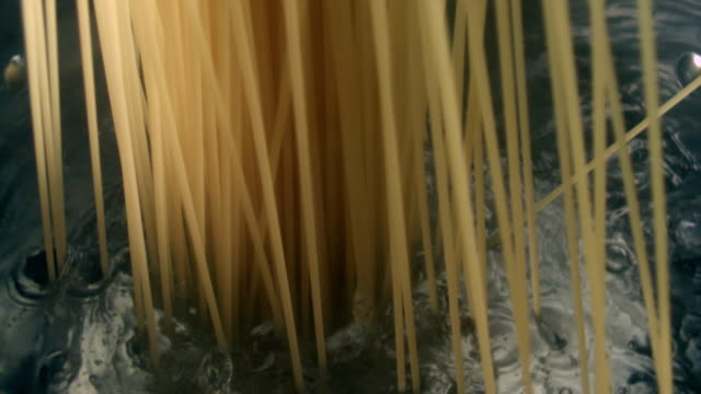 ECU SLO MO Pot of boiling water with uncooked strands of pasta falling in / Seoul, South Korea