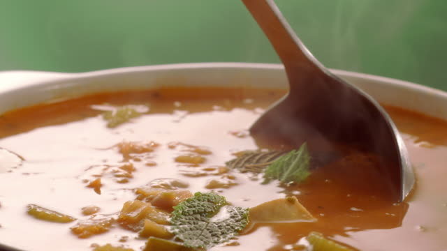 stockvideo's en b-roll-footage met cu pot of fish soup as ladle scoops out a serving with chunks of white fish, vegetables and beans - handen in een kommetje