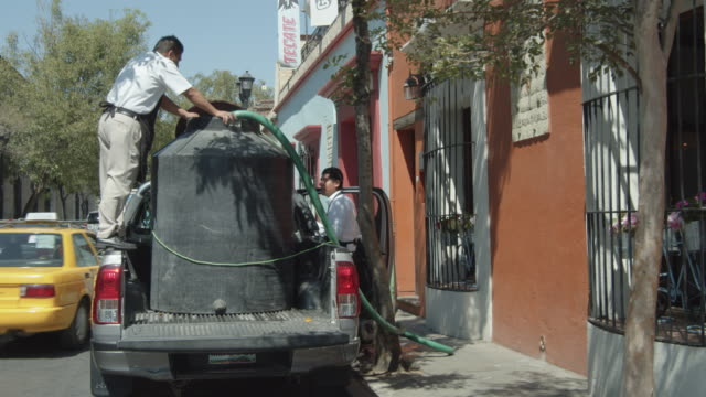 potable water service company at oaxaca, mexico. two men using a hose to bring water from the tank to the house - water conservation stock videos & royalty-free footage
