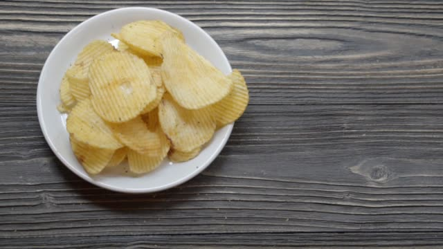 Potato chip fried crisp on dish on the wood table, snack food appetizer with delicious and tasty but unhealthy, moving motion.