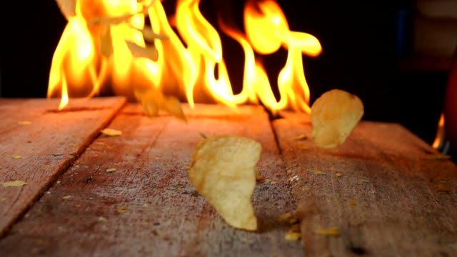 ポテトチップは、火にスローモーションを注ぐ - 塩味スナック点の映像素材/bロール