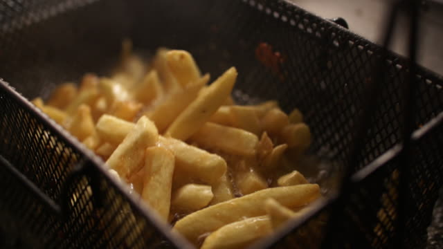 CU SLO MO potato chips cooking in deep fryer/ Johannesburg/ South Africa