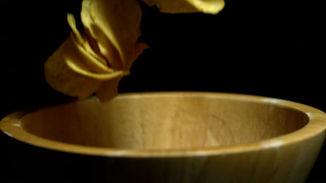 potato chips falling into wooden bowl - crisps stock videos & royalty-free footage