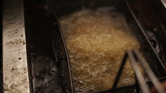 cu slo mo potato chips in deep fryer getting lowered into hot oil/ johannesburg/ south africa - 塩味スナック点の映像素材/bロール