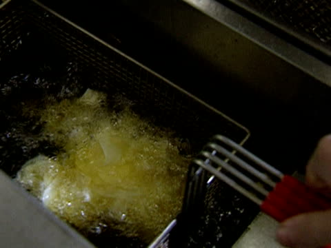 potato crisps are fried in a deep fat frier - fried potato stock videos and b-roll footage