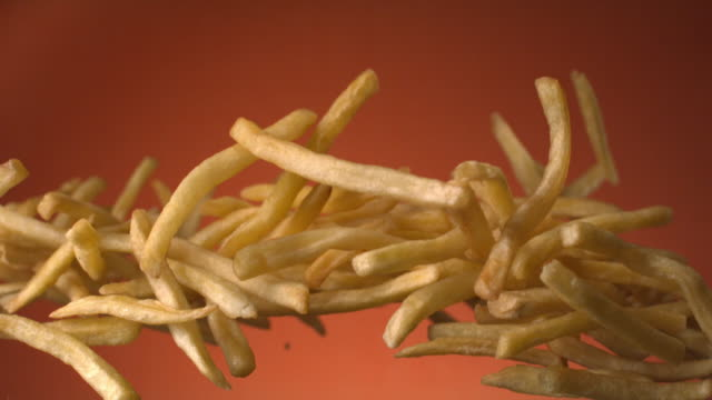 vídeos y material grabado en eventos de stock de potato french fries flying in the air on a terra cotta background shot on phantom at 1500 fps - volar