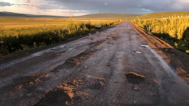 potholes on the alaska dalton highway at sunset - gravel stock videos & royalty-free footage