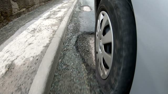 4k: potholes on very damaged road - driving over, view from the tyre - asphalt stock videos and b-roll footage