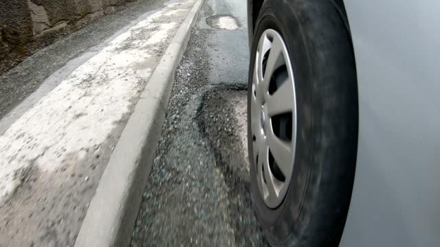 4K: Schlaglöcher auf sehr beschädigte Straße - überfahren, vom Reifen anzeigen
