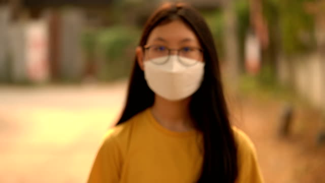 potrait of sick girl wearing pollution mask walking to the camera - pollution mask stock videos & royalty-free footage