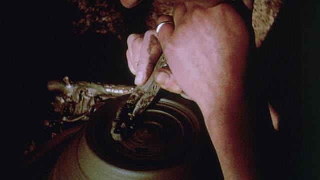 1964 montage potter applying carving tool, sculpting an urn while turning on pottery wheel / aldermaston, berkshire, england - aldermaston stock videos & royalty-free footage