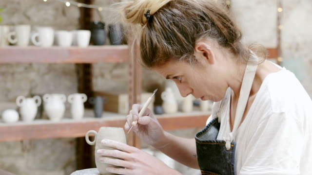 potter carving on clay vase with tool at studio - side hustle stock videos & royalty-free footage