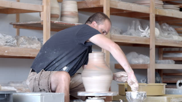 ms potter in pottery studio at pottery wheel dips sponge into water cup and presses wet sponge against spinning vessel to shape its neck   / palm springs, california, usa - potter stock videos & royalty-free footage