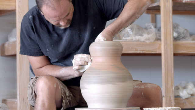 ms potter in pottery studio at pottery wheel shaping the neck of large clay vase / palm springs, california, usa  - pottery stock videos & royalty-free footage