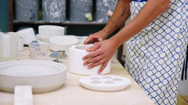 stockvideo's en b-roll-footage met pottenbakker die kleipotten in aardewerkstudio maakt - carving craft product