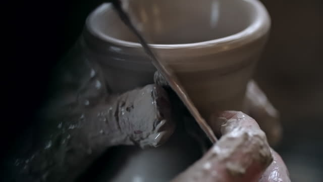 Potter removing excess clay from jug
