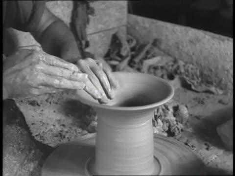 a potter shapes a pot using a potter's wheel - keramiker stock-videos und b-roll-filmmaterial