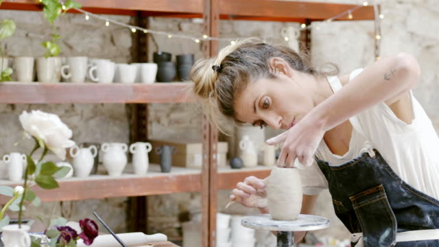 potter shaping vase with work tool at studio - potter stock videos & royalty-free footage