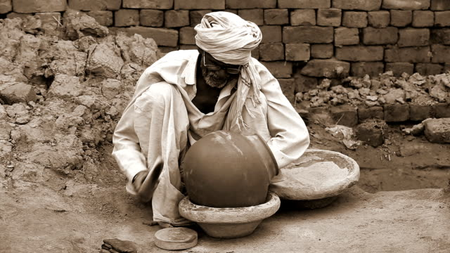 potter sitting at home and shaping a pot - south asia stock videos & royalty-free footage