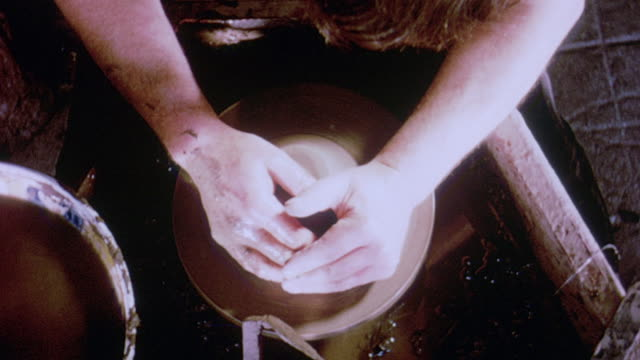 1964 montage potter swishing hand in bowl of water, applying water to ball of clay on pottery wheel and throwing, shaping clay ball / aldermaston, berkshire, england - potter stock videos & royalty-free footage
