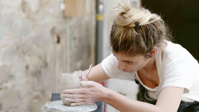 ポッターのスタジオで粘土の花瓶の作業ツールを使用 - 趣味点の映像素材/bロール