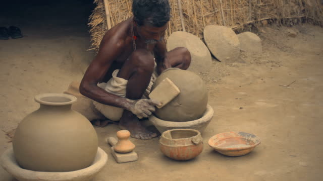 potter works manually in his adobe workshop for the livelihood. - dhoti video stock e b–roll