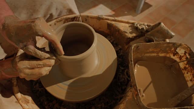 ldポッターの手が車輪の上で回転するボウルの壁を上げる - 陶芸家点の映像素材/bロール