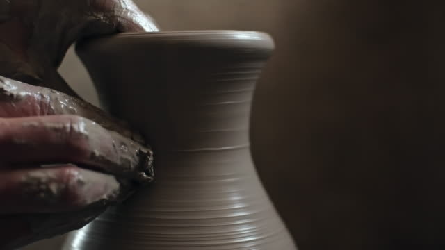 Potter's hands shaping a vase