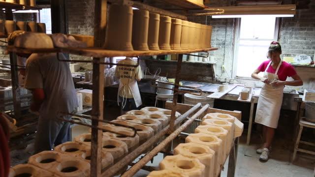 vídeos y material grabado en eventos de stock de potters making mugs in factory - trabajador de línea de montaje