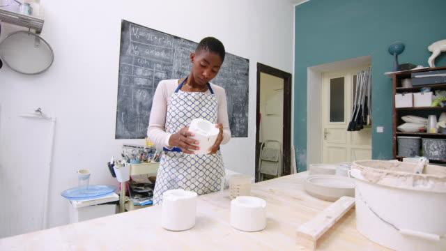 vídeos y material grabado en eventos de stock de fabricante de cerámica inspeccionando moldes de fundición en taller - una mujer de mediana edad solamente