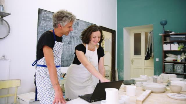 keramikladen-partner arbeiten gemeinsam an einem laptop - werkstatt stock-videos und b-roll-filmmaterial