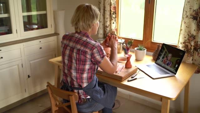 insegnante di ceramica che ha una lezione online da casa - prodotti in ceramica video stock e b–roll