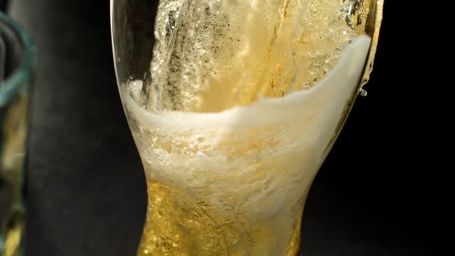 Pouing beer into glass. Bubbles and froth