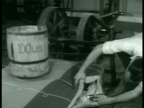 manufacturing 100 pound barrel on mattress man observing textiles machine testing strength of material food production peeled cleaned vegetables... - anno 1938 video stock e b–roll