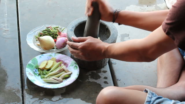 pounding garlic in mortar for cooking dinner - thai food stock videos and b-roll footage