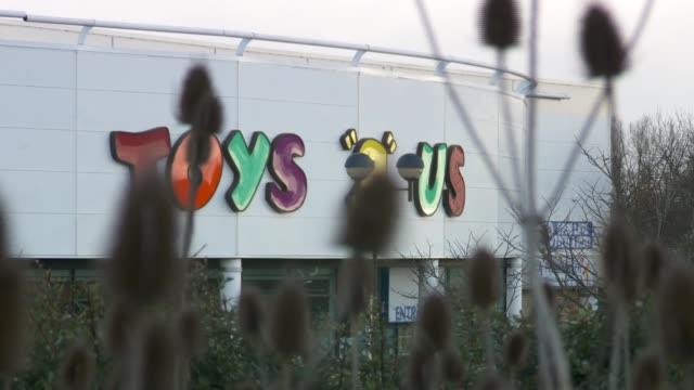 stockvideo's en b-roll-footage met poundworld goes into administration r260218016 / close shot plants with 'toys 'r' us' sign and shop in background - toys r us