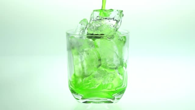 vídeos de stock e filmes b-roll de pour green water into the glass with ice white background. - juicy